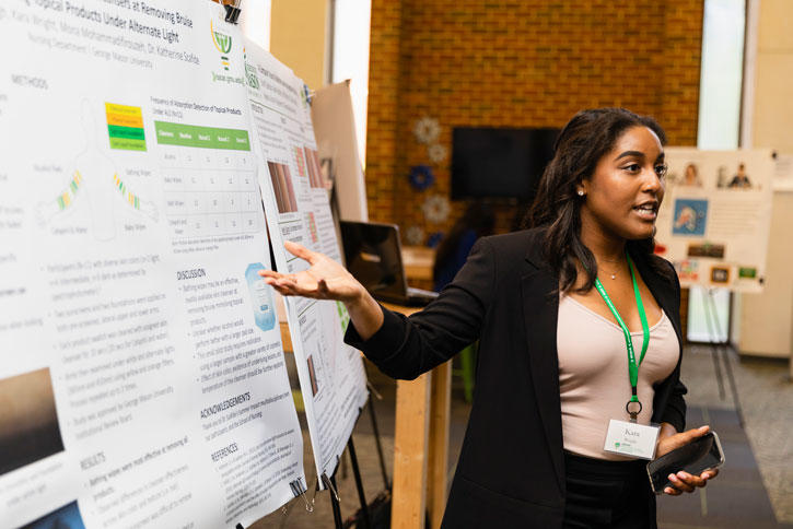 Senior Kara Wright talks about a summer research project during the OSCAR Summer Celebration in the MIX at Fenwick on Mason's Fairfax Campus. The event included 70 poster presentations by 113 students.